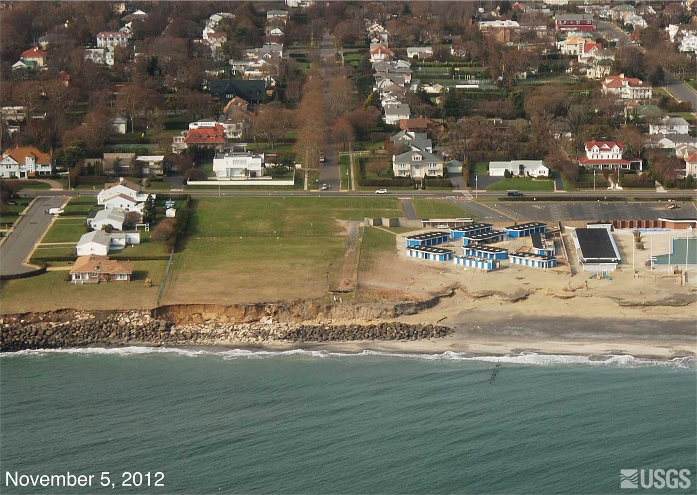After Hurricane Sandy, erosion of the low cliff indicates overtopping of the rock shore protection structures. The yellow arrow in each image points to the same feature. (USGS)